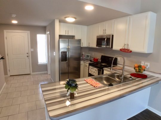 The beautifully redesigned kitchen is in the townhouse at Pepper Tree Condominiums, and features stainless appliances, brand new white cabintry and ultra modern counertops and fixtures.